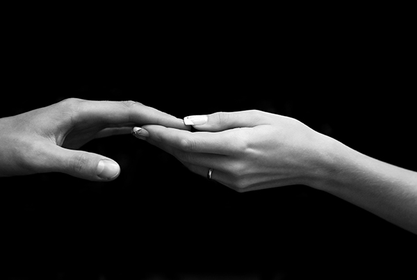 Man's and female hand on a black background